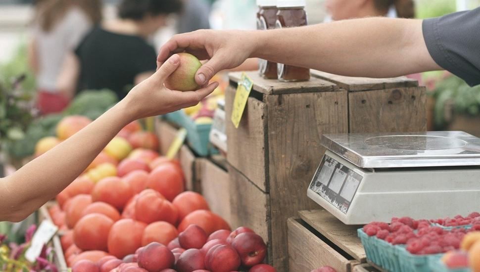 Jedna osoba dodaje drugoj jabuku na pijaci