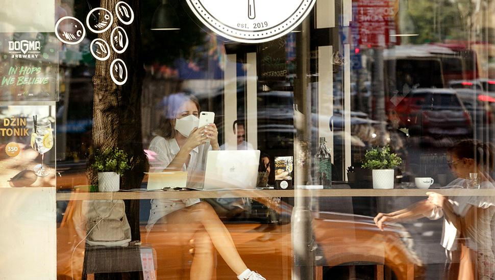 Devojka nosi masku u kafiću i gleda u telefon