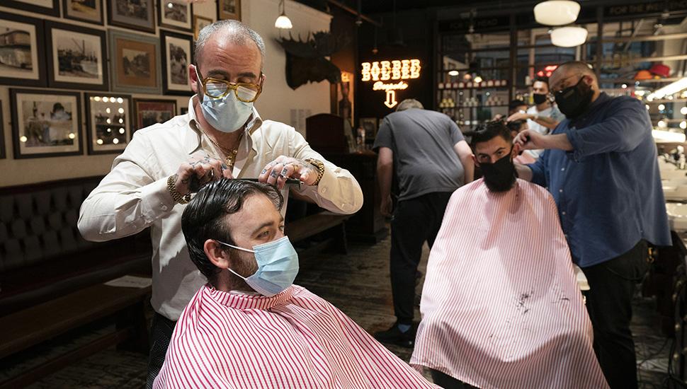Frizer šiša klijenta noseći masku