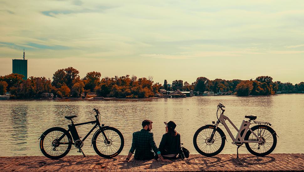 Momak i devojka pored bajseva kraj reke