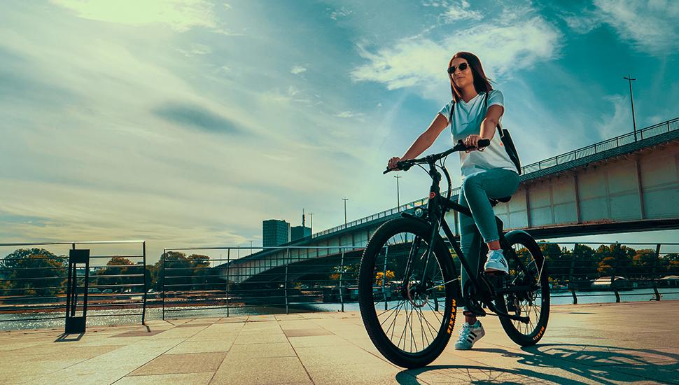 Devojka sedi na električnom biciklu kraj reke