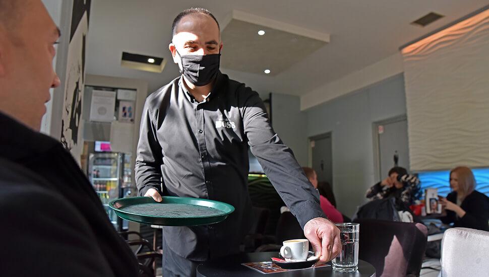 Konobar poslužuje kafu